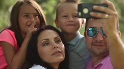 stock-footage-video-of-a-family-taking-selfies-with-smartphone-in-park-shot-in-p-frame-rate